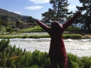 Statue arms outstretched in joy overlooking Esalen.