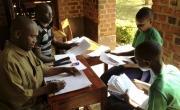 Teachers grading 7th grade students work at school in Tanzania.